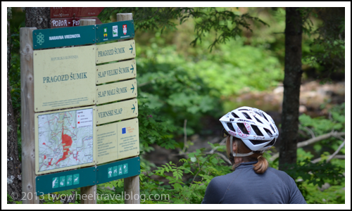 Reading trail signs while bicycle touring Pohorje Transversal trail in Slovenia; Two Wheel Travel